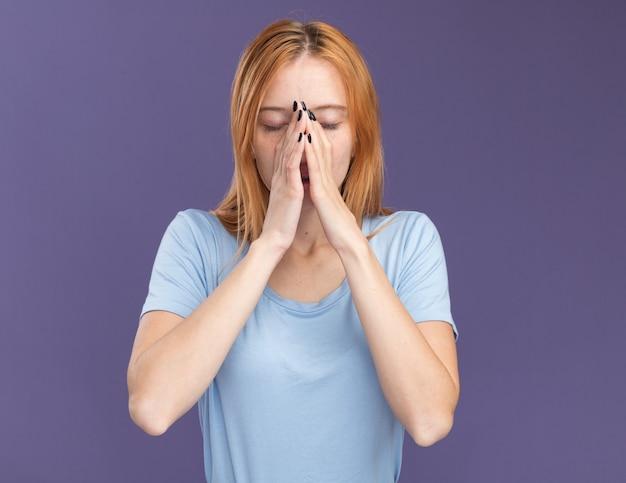Giovane ragazza pacifica dello zenzero rossa con le lentiggini tiene le mani insieme vicino al naso sulla porpora