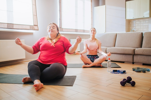 Peaceful young slim and plus size models in lotus pose and meditating