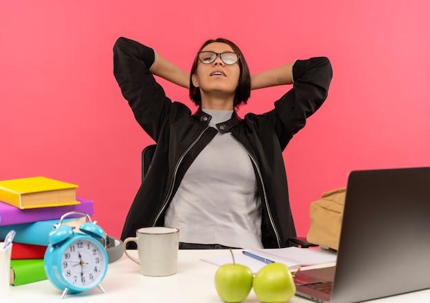 Мирная молодая студентка в очках сидит за столом, положив руки за шею с закрытыми глазами, изолированными на розовом фоне