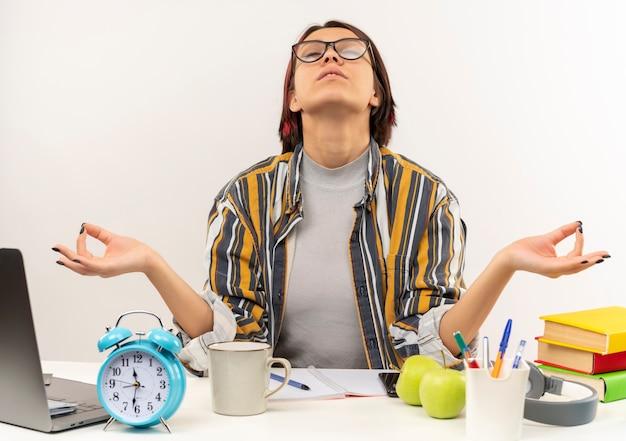 Pacifica ragazza giovane studente con gli occhiali seduto alla scrivania meditando con gli occhi chiusi isolati su sfondo bianco