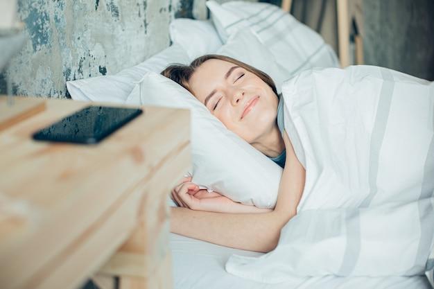 침대에 눈을 감고 누워 행복하게 웃고 있는 평화로운 젊은 여성