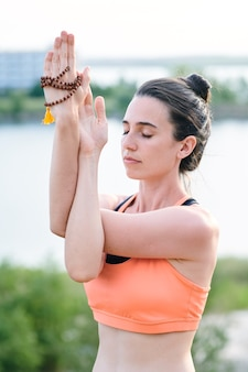 Peaceful young woman with closed eyes twisting arms while doing eagle pose outdoors