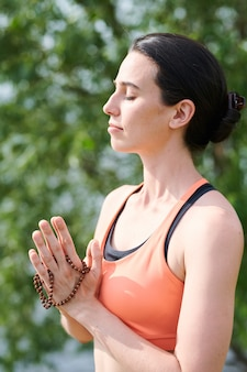 Peaceful young woman with dark hair standing outdoors and meditating with yoga mala beads