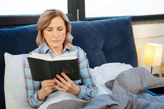 평화롭게 성경을 읽으십시오. 오픈 성경을 들고 파자마에 누워있는 동안 신중하게 읽는 긍정적 인 진정 여자