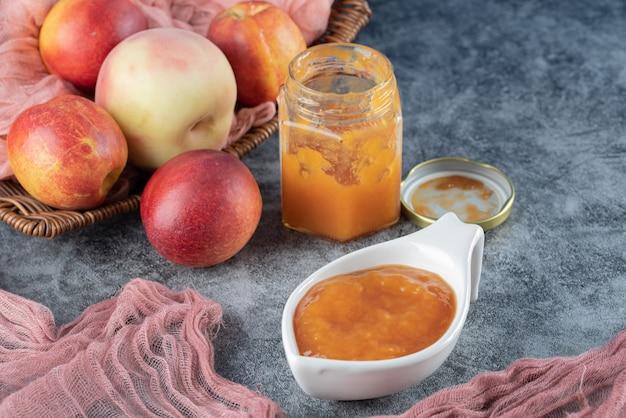 흰색 컵 옆에 노란색 컨피츄어가 있는 분홍색 수건 조각에 나무 바구니에 복숭아와 사과