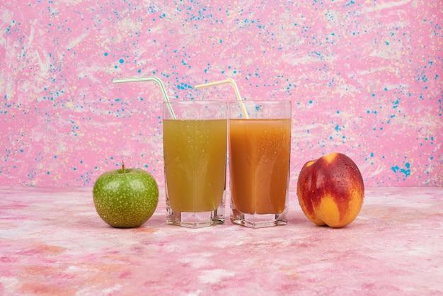 주스 컵과 복숭아와 사과.