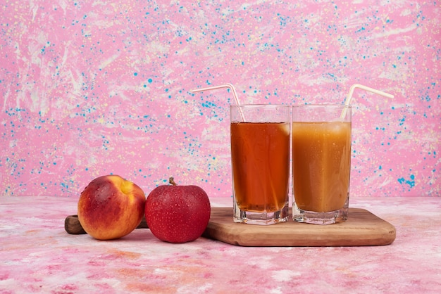 Peach and apples with cups of juice.