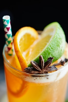 Peach black iced tea consists of vanilla syrup, spices and lemon juice in a glass closeup on dark background