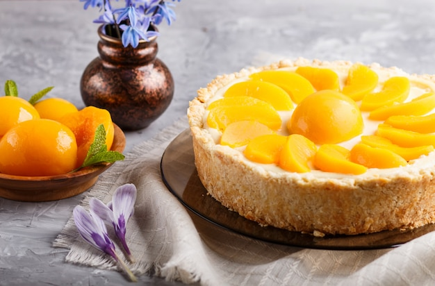 Peach cheesecake and ceramic vase with blue flowers on gray