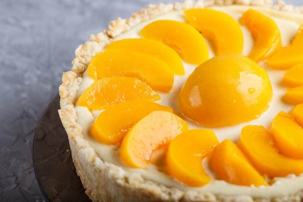 Peach cheesecake on a gray concrete background.