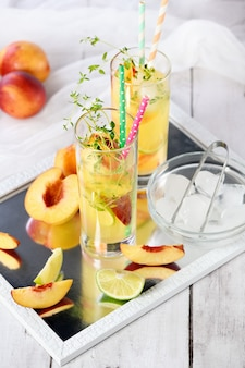Peach cocktail refreshing organic nonalcoholic drink lemonade with ripe nectarine thyme and lim