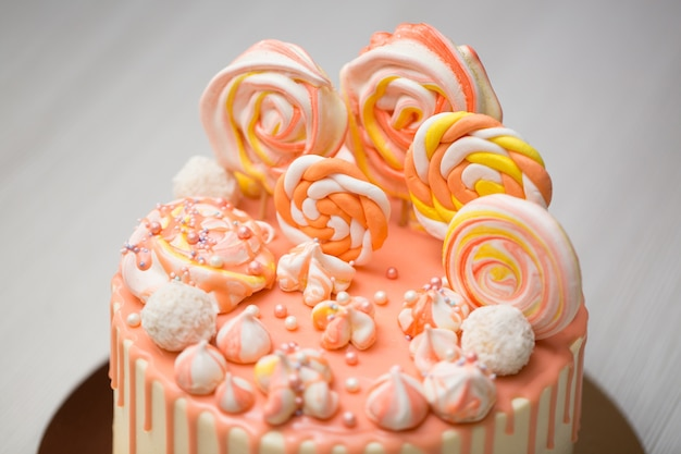 Peach colored cake with meringue, candy, chocolate stains and jelly beans