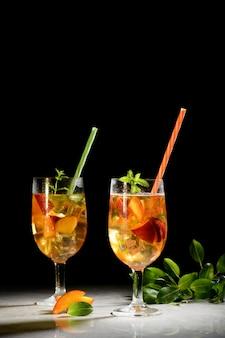 Персиковый свежий чай со льдом, персиковый летний безалкогольный коктейль на черном столе. янтарное вино, сангрия с персиком и мятой, крупным планом и копией пространства