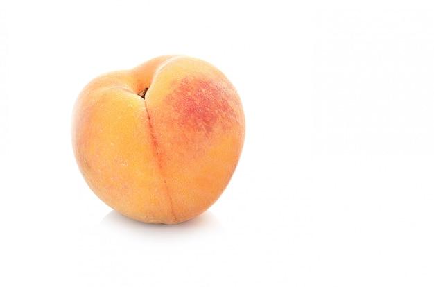 Половина персика с листом, изолированная на белой стене
