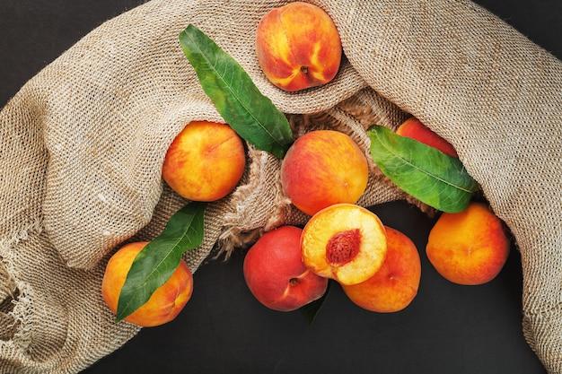 黄麻布と緑の葉の布で黒の桃の果実