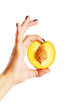 Peach fruit in woman's hand