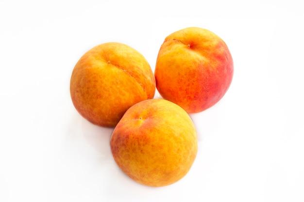 Изолированная коллекция плодов персика. спелые персики на белом фоне и фоне дерева