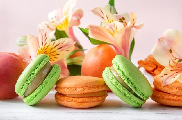 노란색 alstroemeria 꽃과 복숭아, 녹색 마카롱 쿠키, 베이지 색 표면에 신선한 살구