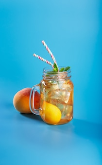 Peach ice tea on blue background with mint and ice, nice drink for summer hot season
