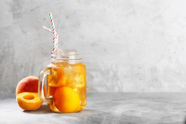 Персиковый ледяной чай в банке mugor на бетонном сером фоне с мятой и льдом
