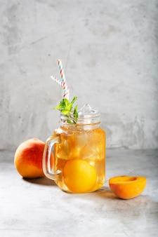 Персиковый холодный чай на бетонном сером фоне с мятой и льдом