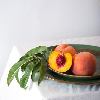 테이블 위의 색상 녹색 접시에 잎이 있는 미니멀한 스타일의 복숭아에 뼈가 있는 반으로 복숭아...