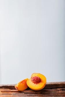 骨で半分に桃。熟したジューシーな桃。白い背景の上の現代の静物。