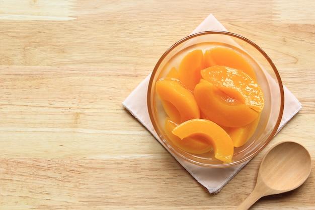 Персик в сиропе и деревянной ложкой на столе