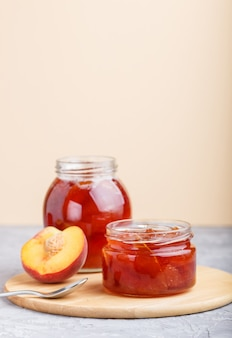 Peach jam in a glass jar with fresh fruits on gray concrete background. side view.