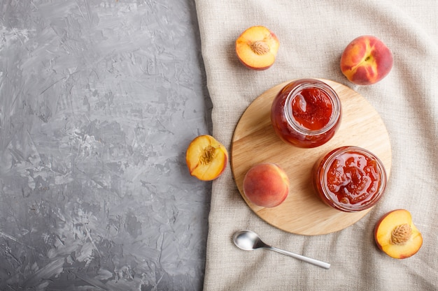 Peach jam in a glass jar with fresh fruits on gray concrete background. top view.