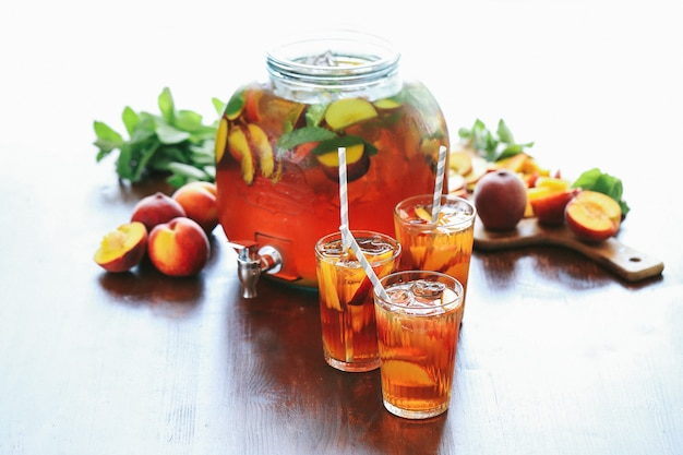 Peach juice in cups and in a big jar with fruit slices inside
