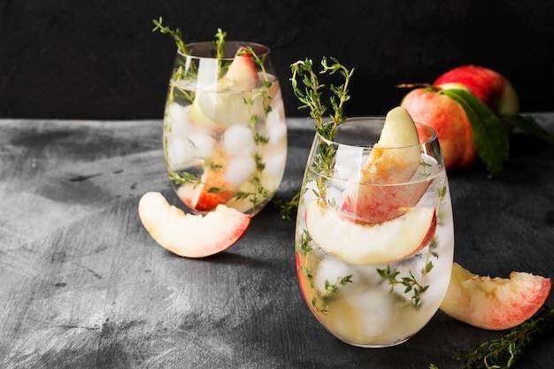 Peach lemonade with thyme on a dark background.