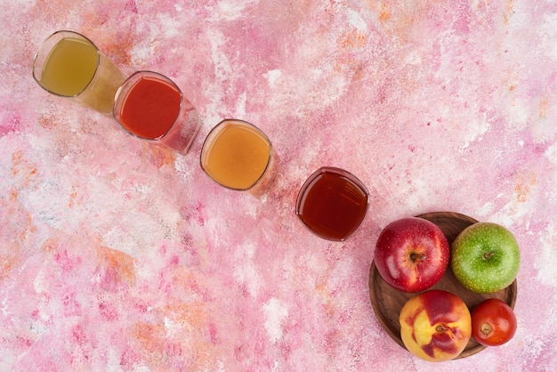 Peach, lemonnd apples with cups of juice on wooden board.