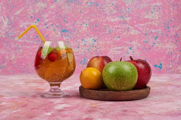 중앙에 나무 보드에 주스 컵과 복숭아, lemonnd 사과.
