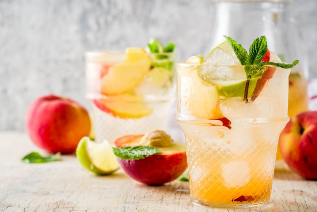 Peach and lime lemonade, mojito cocktail with fresh fruit garnish, om light concrete table