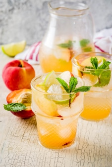 Peach and lime lemonade, mojito cocktail with fresh fruit garnish