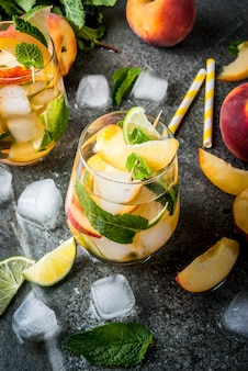Peach mojito with lime, peach and mint on a dark stone table.