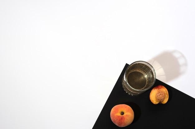 Персиковый нектарин и стакан персикового сока на черно-белом фоне в плоском стиле с копией