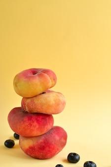 黄色の背景に桃。ジューシーな熟した桃とブルーベリー。創造的なミニマルな食品のコンセプト。