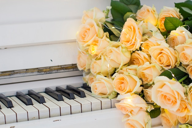 Peach roses with garlands on a white piano