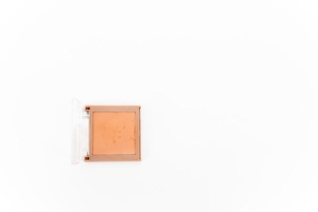 복숭아 색조는 흰색 배경에 격리된 컴팩트한 정사각형 케이스에 파우더를 직면합니다. 뷰티 컨셉