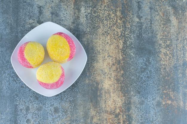Biscotti fatti in casa a forma di pesca sul piatto, sulla superficie di marmo.