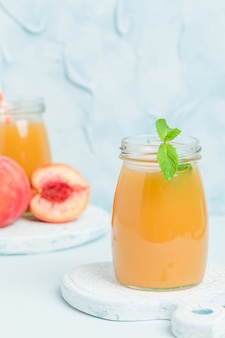 Peach smoothie in glass jars with fresh ripe fruits and green mint leaves on blue pastel background