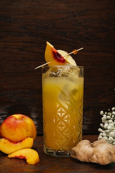Peach summer cocktail or lemonade with ginger cold refreshment drink with in glass