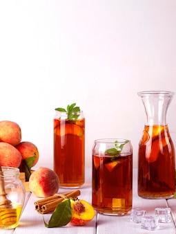 Летний холодный напиток персиковый чай с кубиками льда и мятой на белом фоне выборочный фокус