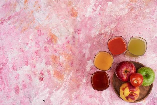 Pesche, pomodori e mele con tazze di succo su tavola di legno, vista dall'alto.