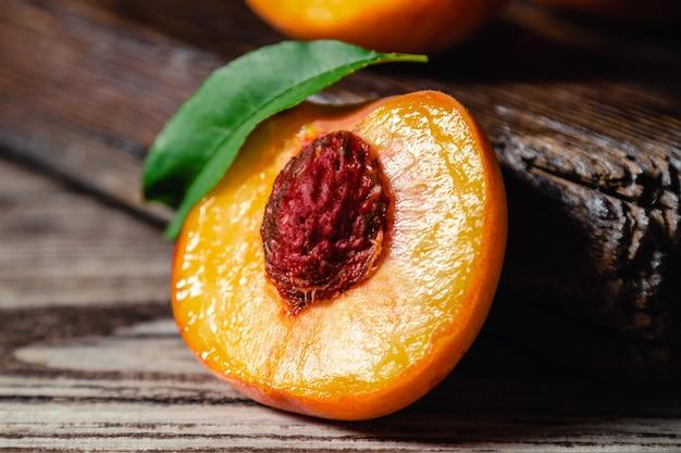 Персик с листом на деревянном столе. персик пополам. спелые сочные персики. урожай персиков для еды или сока. крупный план.