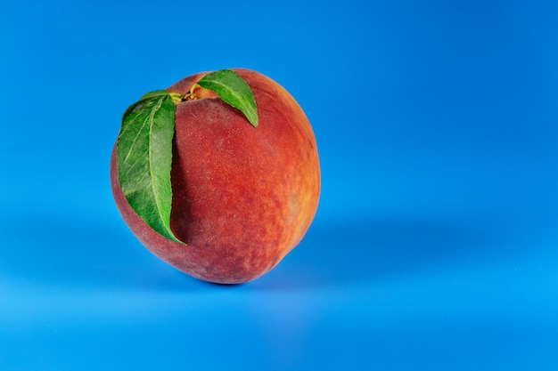 Peach with leaves isolated on blue background