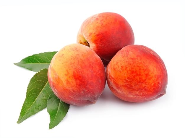 Персик с листьями на белом