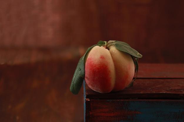 木製のテーブルの上に、葉と桃
